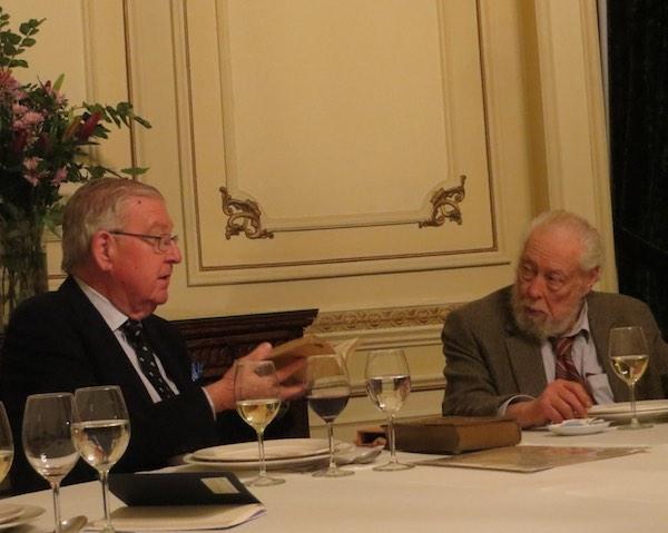 Roberto Guzmán Lyon expone acerca de un libro de su colección. Hugo Zepeda escucha atentamente.